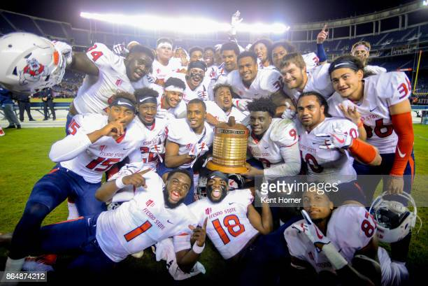 Members of the Fresno State Bulldogs football celebrate with the school rivalry Oil Can Trophy after winning the game against the San Diego State...