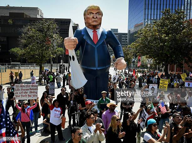 Members of the 'Full Rights for Immigrants Coalition' display a giant effigy of US Republican Party presidential hopeful Donald Trump during a...