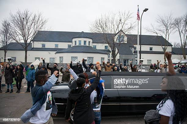 Members of the funeral procession for Jamar Clark drive by as protesters raise fists outside the 4th Precinct Minneapolis Police station on November...