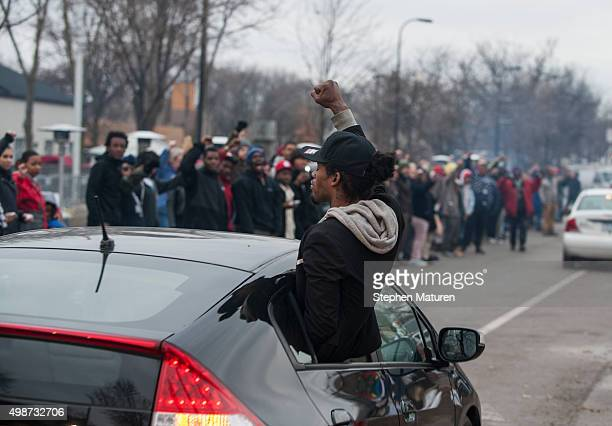 Members of the funeral procession for Jamar Clark join protestors raising their fists outside the 4th Precinct Minneapolis Police station on November...