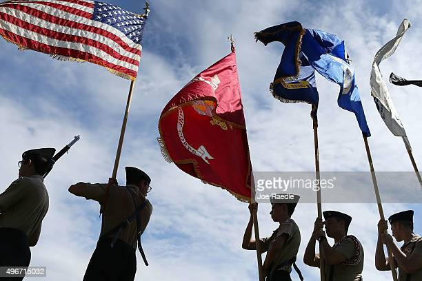 Members of the G Holmes Braddock Senior High School NJROTC color guard carry their flags during a Veterans day ceremony on November 11 2015 in Miami...