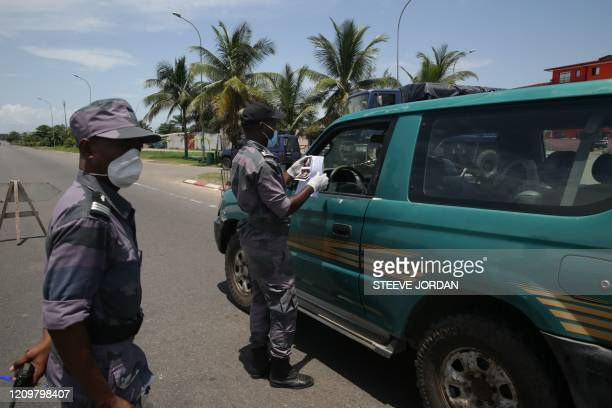 Members of the Gabonese Gendarmerie are controls the papers of a motorist coming from the hospital at a checkpoint in Libreville on April 13, 2020...