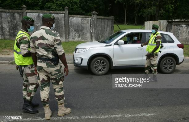 Members of the Gabonese Presidential Guard are seen stopping a car at a checkpoint in Libreville on April 13, 2020 while checking residents during a...