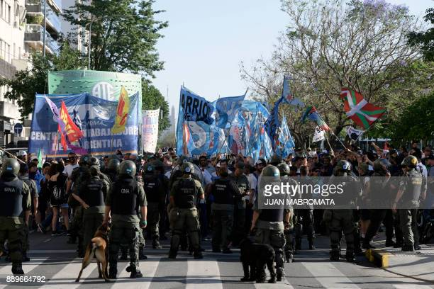 Members of the Gendarmerie stand in close formation to stop demonstrators from social organizations and Argentina's Central Workers' Union marching...