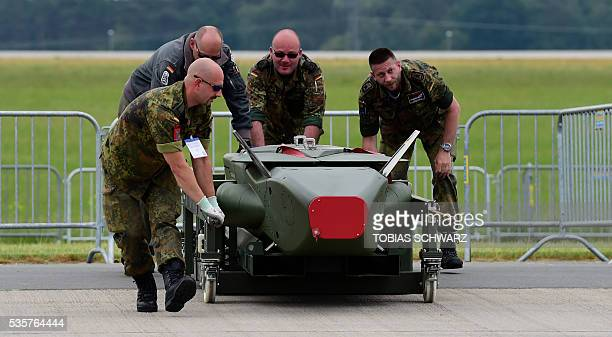 Members of the German Armed Forces Bundeswehr carry a 'Taurus' weapon system the International Aerospace Exhibition in Schoenefeld on May 30 2016 The...