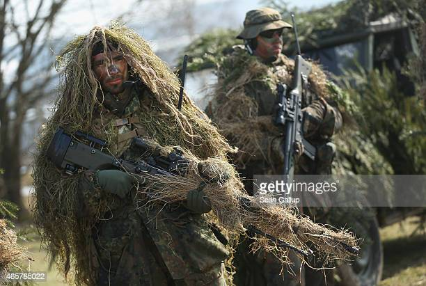 Members of the German Bundeswehr's 371st Armoured Infantry Battalion stand in camouflage with sniper rifles during a media event at the battalion's...