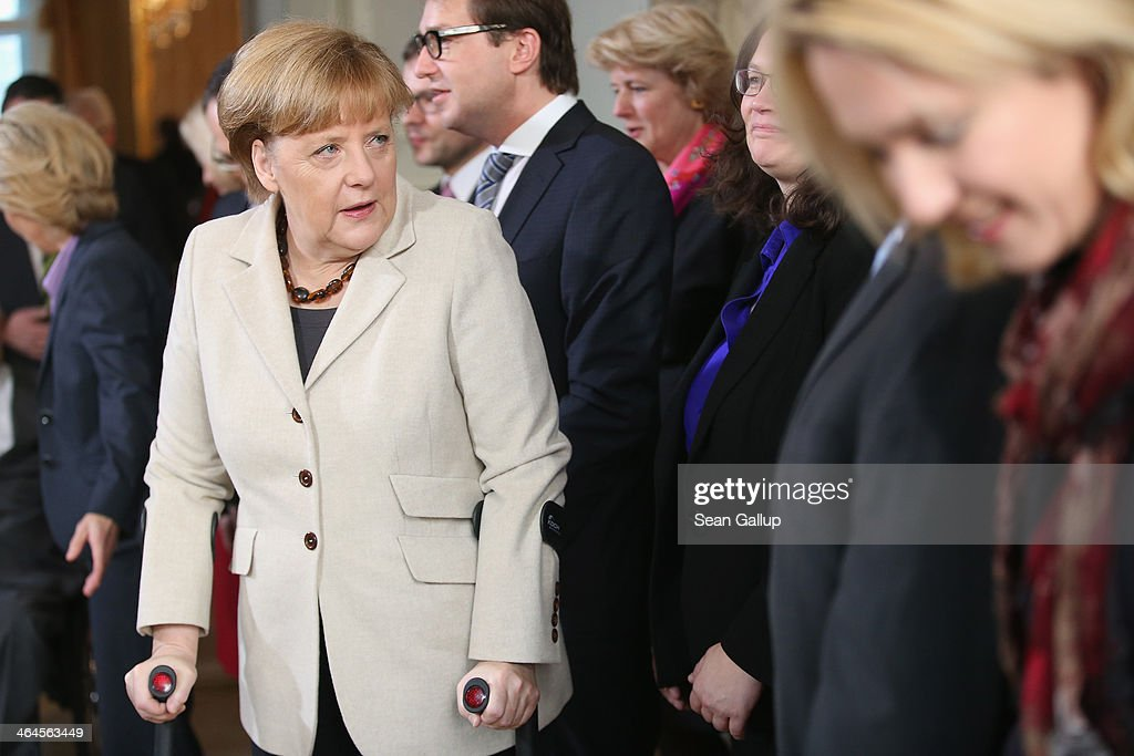 Members of the German government cabinet, including Chancellor Angela Merkel, walking with crutches due to a cross-country skiing injury, arrive for a group photo on day two of meetings of the cabinet at Schloss Meseberg palace on January 23, 2014 in Meseberg, Germany. The government cabinet of Christian Democrats and Social Democrats is on a two-day retreat at Meseberg.