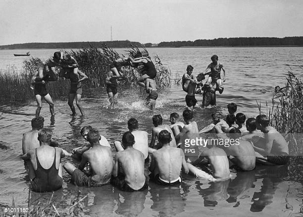 Members of the German Hitler Youth organization enjoy piggy-back fights at the edge of the Ruppiner See near Neuruppin, Germany, during a summer...