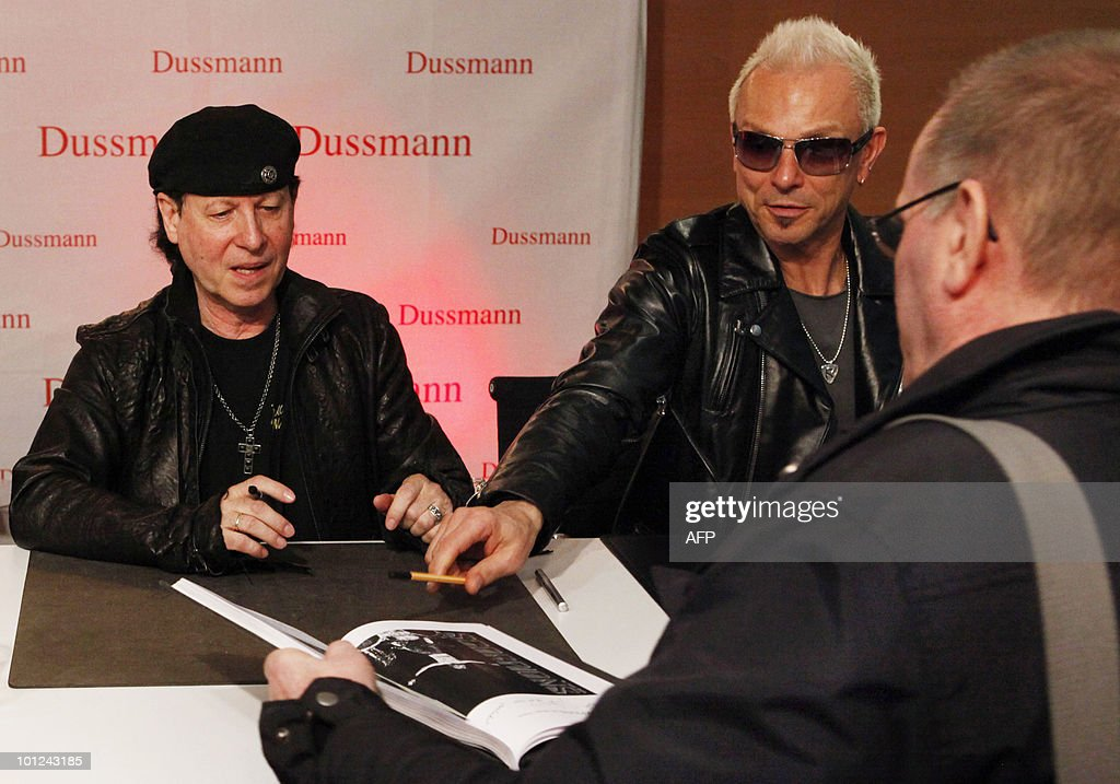 Members of the German rock band Scorpions including Klaus Meine (L) and Rudolf Schenker sign books for fans after a press conference on May 28, 2010 at the Dussmann bookshop in Berlin during the presentation of a new coffee-table book by photographer Marc Theis. The photographer accompanied the band on their world tour from 2007 to 2009.