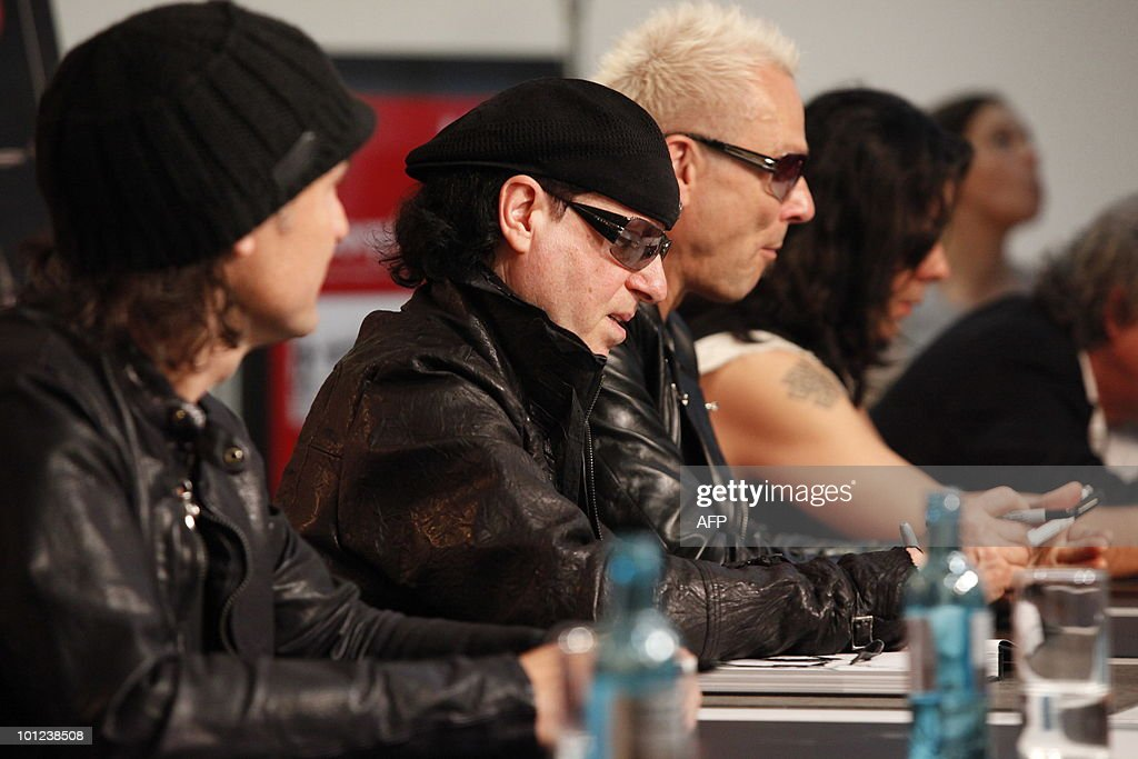 Members of the German rock band Scorpions including Klaus Meine (C) sign books for fans after a press conference on May 28, 2010 at the Dussmann bookshop in Berlin during the presentation of a new coffee-table book by photographer Marc Theis. The photographer accompanied the band on their world tour from 2007 to 2009.