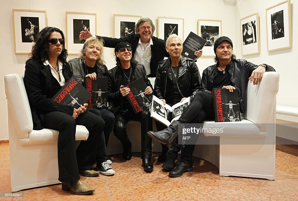 Members of the German rock band Scorpions (L-R) Pawel Maciwoda, James Kottak, Klaus Meine, Rudolf Schenker and Matthias Jabs pose for photographers before a press conference on May 28, 2010 at the Dussmann bookshop in Berlin during the presentation of a new coffee-table book by photographer Marc Theis (back). The photographer accompanied the band on their world tour from 2007 to 2009.