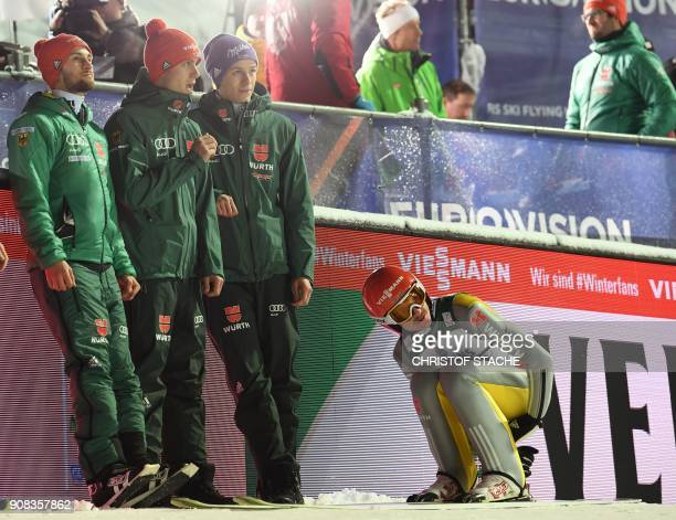 Members of the German team Andreas Wellinger Markus Eisenbichler Stephan Leyhe and Richard Freitag react after the last jump of the team competition...