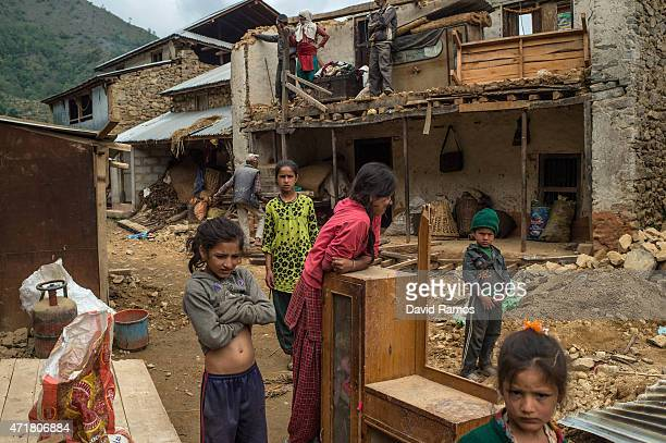 Members of the Ghomenath Chaulagain family work on the resconstruction of their family home on May 1 2015 in Bhotechaur Nepal A major 78 earthquake...