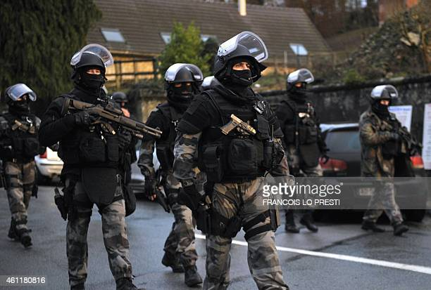 Members of the GIPN and RAID French police special forces walk in Corcy northern France on January 8 2015 as they carry out searches as part of an...