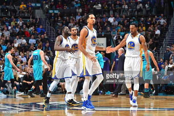 Members of the Golden State Warriors give each other fives against the Charlotte Hornets at Spectrum Center on January 25 2017 in Charlotte North...