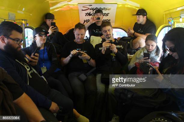 Members of the GoPro team and media take a moment on a bus to check out video of San Francisco adventures captured using freshlyreleased Hero 6...