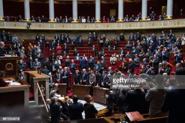 Members of the government and Parliamentaries applaud as they stand in tribute to late French singer Johnny Hallyday who died overnight aged 74 at...