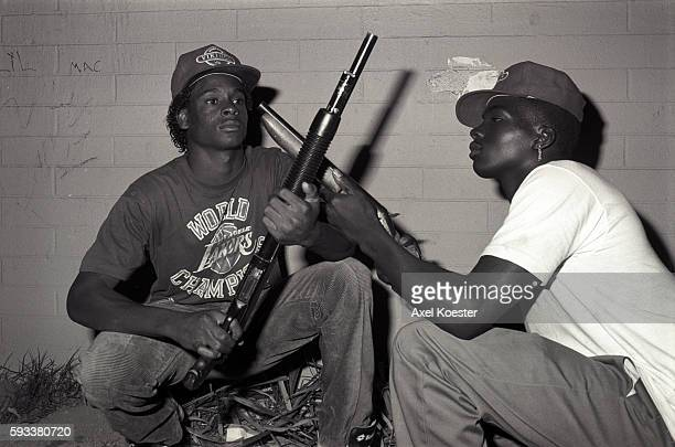 Members of the Grape Street Watts Crips pose with their shotguns and wear their gang's signature Vikings baseball caps The Grape Street Watts Crips...