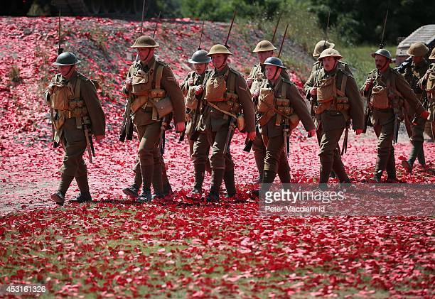 Members of the Great War Society living history group dressed as 4th Battalion the Middlesex Regiment march through a poppy strewn field after a...