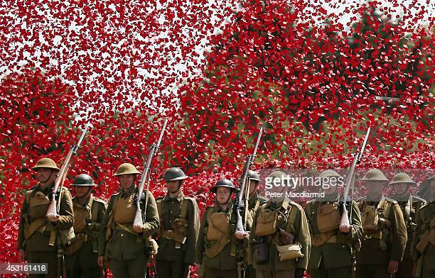 Members of the Great War Society living history group dressed as 4th Battalion the Middlesex Regiment stand under a shower of a million poppy flowers...