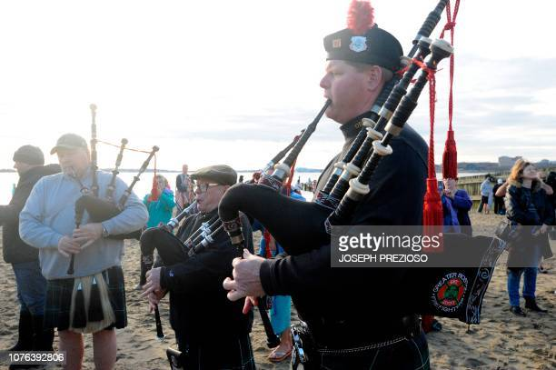 Members of the Greater Boston Fire Fighters Pipe and Drum Core play music at the end of the annual L Street Brownies New Year's Day Plunge at the...