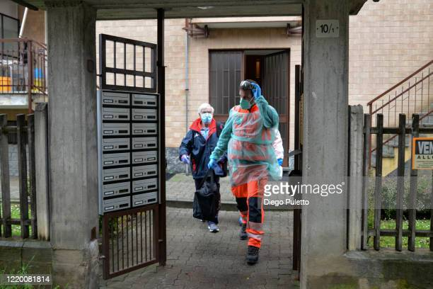 Members of the Green Cross of Vinovo wear protective suits during the transportation of a coronavirus patient during the nationwide lockdown on April...