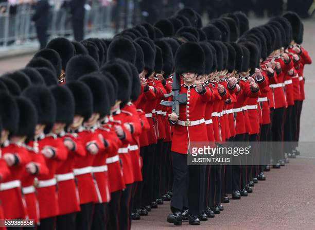 Members of the Grenadier Guards march past Buckingham Palace ahead of the Queen's Birthday Parade 'Trooping the Colour' in London on June 11 2016...