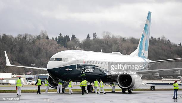 Members of the ground crew check out a Boeing 737 MAX 8 airliner after it landed at Boeing Field to complete its first flight on January 29 2016 in...