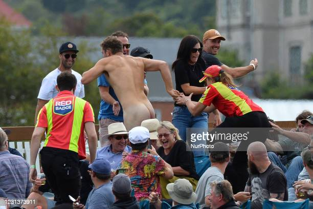 Members of the ground security try to catch a streaker during the second Twenty20 international cricket match between New Zealand and Australia at...