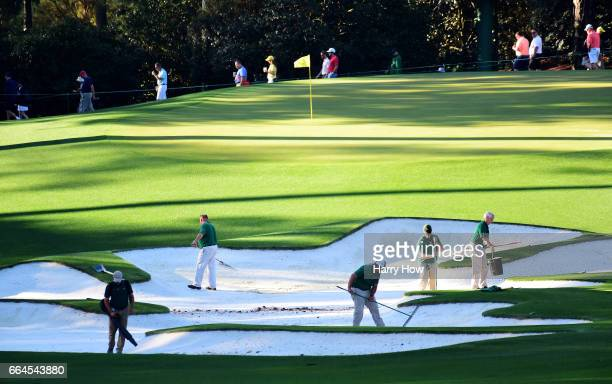 Members of the grounds crew tend to a bunker on the tenth hole during a practice round prior to the start of the 2017 Masters Tournament at Augusta...