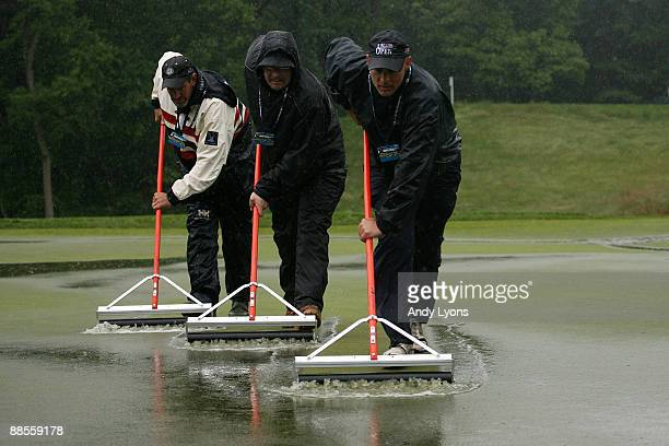 Members of the grounds crew work on a soggy green during the first round of the 109th U.S. Open on the Black Course at Bethpage State Park on June...