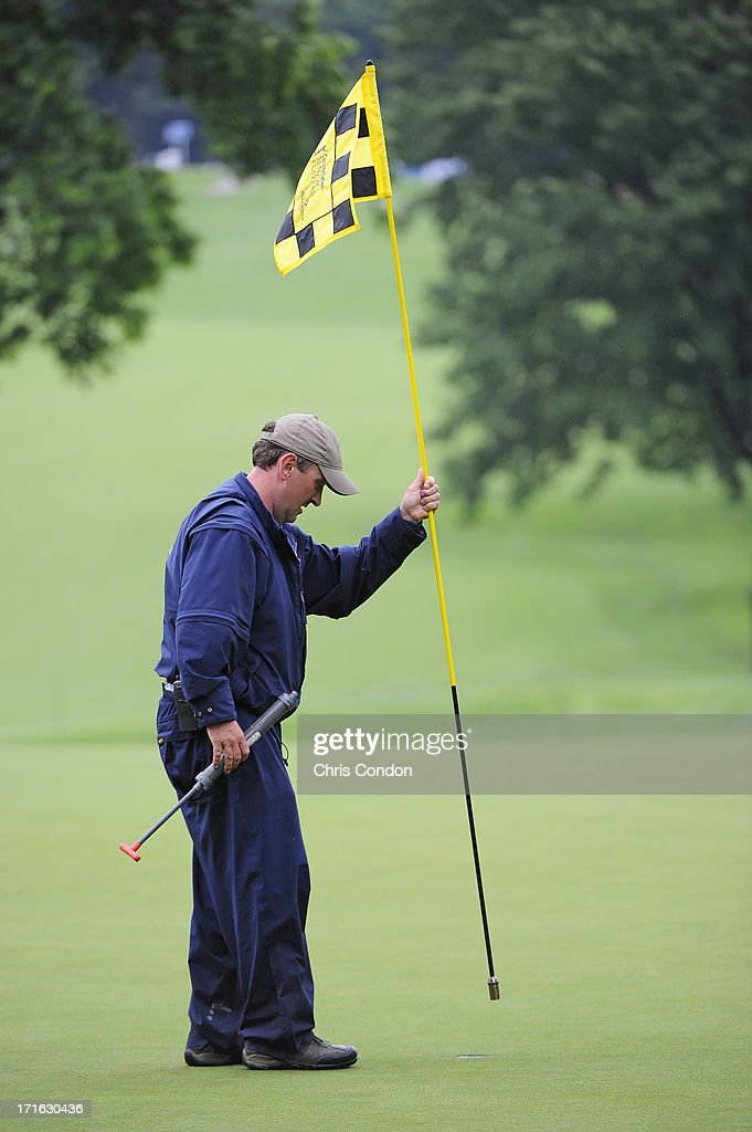A members of the grounds staff places the pin flag on the 12th green after heavy rains caused a delay during the first round of the Constellation SENIOR PLAYERS Championship at Fox Chapel Golf Club on June 27, 2013 in Pittsburgh, Pennsylvania.