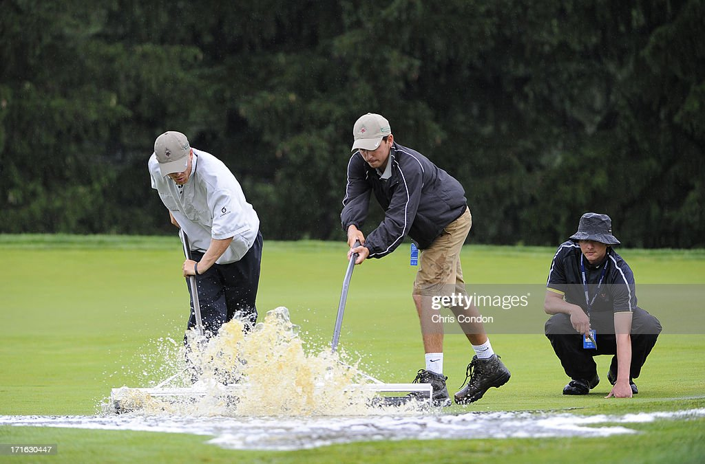 Members of the grounds staff squeegee water from the first green after heavy rains caused a delay during the first round of the Constellation SENIOR PLAYERS Championship at Fox Chapel Golf Club on June 27, 2013 in Pittsburgh, Pennsylvania.