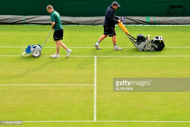 Members of the groundstaff paint the lines and mow the grass on a court before play at The All England Tennis Club in Wimbledon southwest London on...