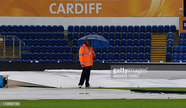 Members of the groundstaff work to protect and drain the pitch as rain delays the start of the 2013 ICC Champions Trophy One Day International...