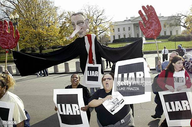 Members of the group 'ACTUP' carry a giant puppet in the likeness of US President Bush during their protest 24 November 2003 in front of the White...