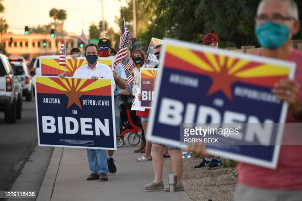 """Members of the group """"Arizona Republicans Who Believe In Treating Others With Respect"""" wave flags and hold signs in support of Democratic..."""