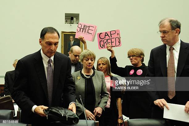 "Members of the group ""Code Pink"" wave signs as Richard S. Fuld Jr., chief executive officer of Lehman Brothers, arrives to testify before the US..."