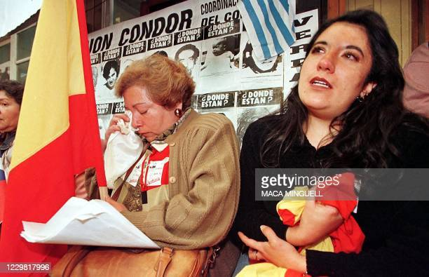 Members of the Group of the Detained and Disappeared who lost relatives during the 1973-1990 dictatorship of Gen. Augusto Pinochet, shed tears of joy...