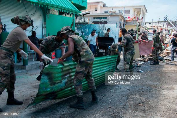 Members of the Guadeloupe Adapted Military Service Regiment gather detritus on September 18 as they clean Sandy Ground on the French Caribbean island...