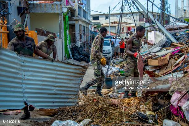 TOPSHOT Members of the Guadeloupe Adapted Military Service Regiment gather detritus on September 18 as they clean Sandy Ground on the French...