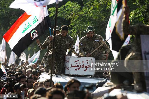 Members of the Hashed alShaabi or Popular Mobilisation Forces paramilitaries stand atop a vehicle carrying the body of the brother of Wissam Alyawi a...