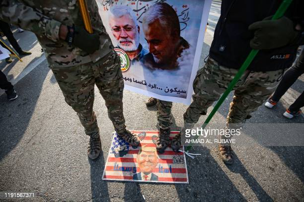 Members of the Hashed alShaabi paramilitary force step on a makeshift US flag bearinga caricature of President Donald Trump during the funeral...