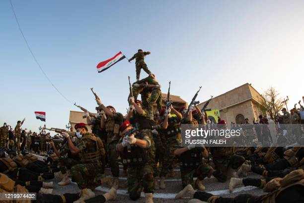 Members of the Hashed al-Shaabi paramilitary force take part in a military parade in the southern Iraqi city of Basra on June 14 marking the sixth...