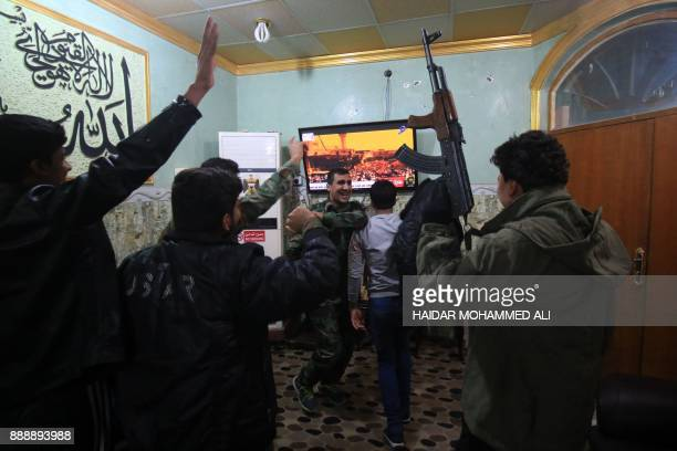 TOPSHOT Members of the Hashed alShaabi watch the televised statement of Iraqi Prime Minister Haider alAbadi in the southern city of Basra on...