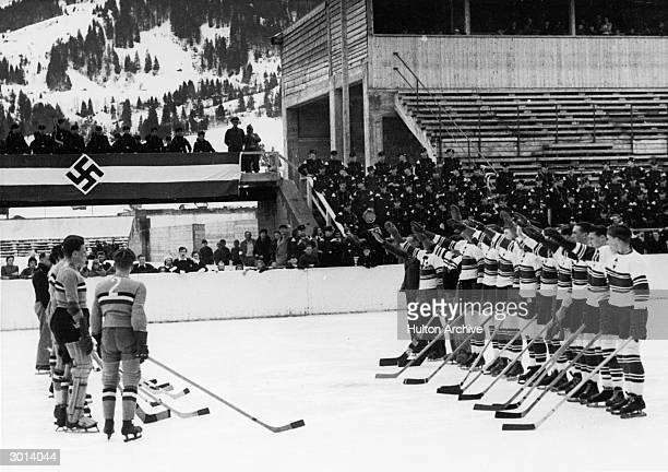 Members of the Hitler Youth hockey team stand in a line on the ice saluting after defeating the Hungarian team in the sixth Hitler Youth Winter Games...