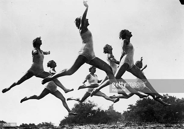 Members of the Hitler Youth leap through the air during health and beauty exercises