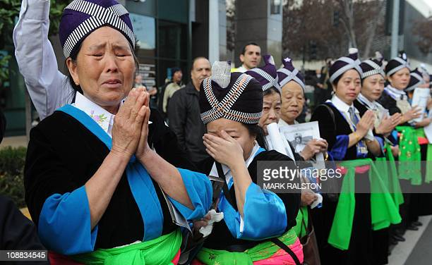 Members of the Hmong community cry as they watch the casket containing Hmong war hero and community leader General Vang Pao on it's horse drawn...