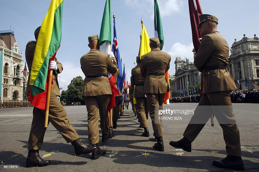 Members of the honor guard march with flags in front of the