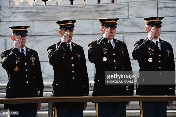 Members of the honor guard salute during a ceremony at the Tomb of the Unknowns at Arlington National Cemetery in Virginia on February 11 2014 During...